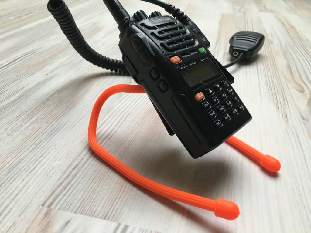 Ein stabilerer Gear Tie als improvisierter Ständer für ein Handfunkgerät